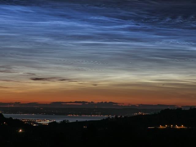Wolken die am Nachthimmel leuchten