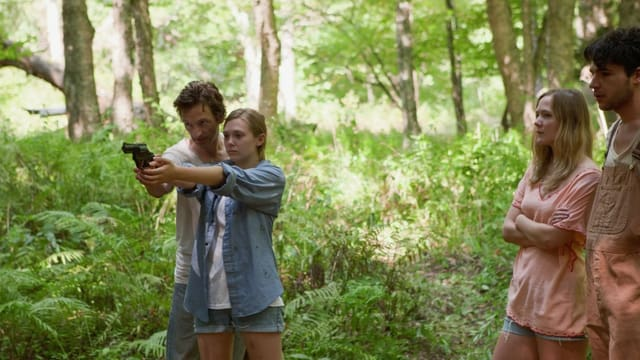 Ein Mann hilft einer Frau mit der Waffe zu zielen.