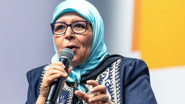 Eine Frau mit Kopftuch spricht in ein Mikrofon.