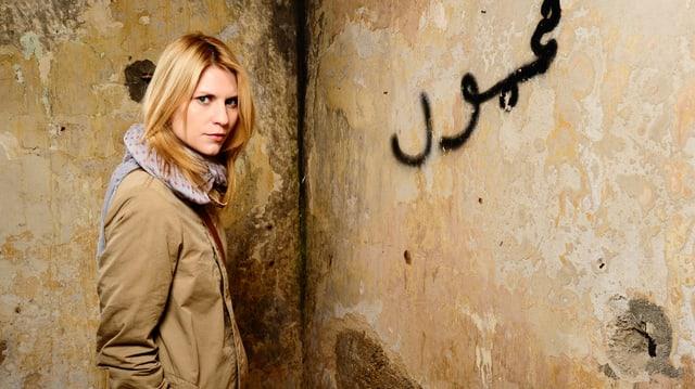 Claire Danes ermittelt als CIA-Agentin Carrie Mathison. Sie steht vor einer verwitterten Wand, auf der arabische Schriftzeichen stehen.