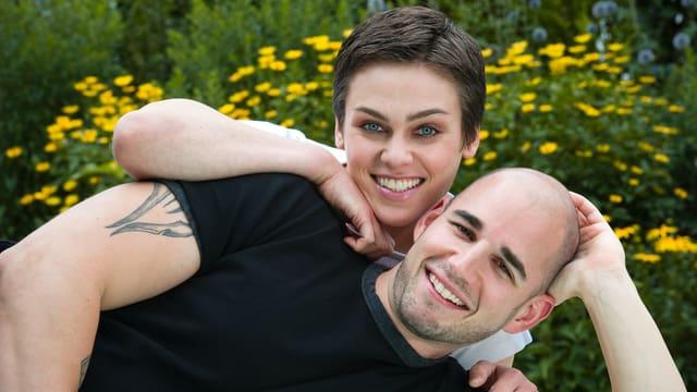 Paar liegt auf der Wiese und lächelt in die Kamera