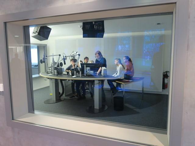 Kinder und ein Redaktor sind durch eine Glasscheibe im Radiostudio zu sehen.