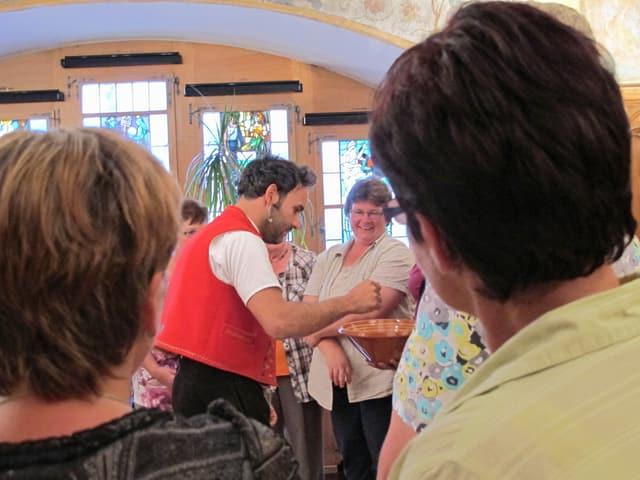 Gruppe von Frauen, in der Mitte steht Marcel Koller und zeigt einer Teilnehmerin wie man Taler schwingt.