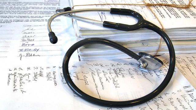 Ein Stethoskop liegt auf handbeschriebenen Blättern.