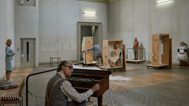 Theaterszene: Ein Mann sitz an einem kleinen Klavier, im Hintergrund einsame Menschem und fahrende Kisten.