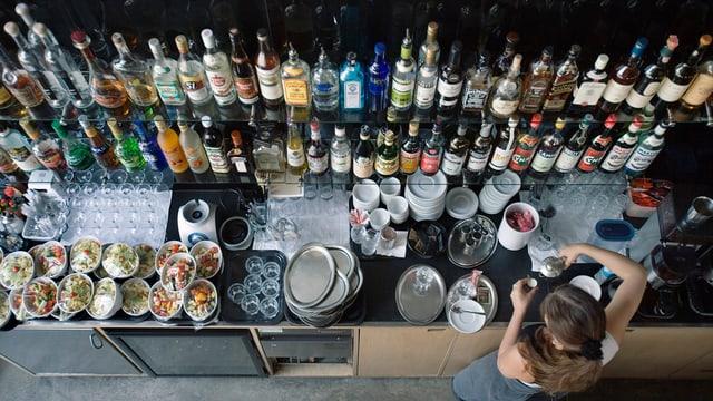 Frau an einer Bar in einem restaurant. Bild aus der Vogelperskeptive; die Frau erkennt man kaum, man sieht aber die Bar mit sehr vielen Alkoholflaschen und auf dem Tisch darunter stehen auch einige bereits zubereitete Speisen.