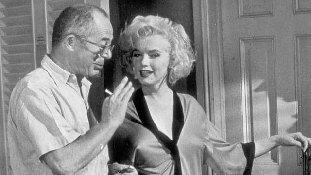 Billy Wilder unterhält sich mit Marilyn Monroe.