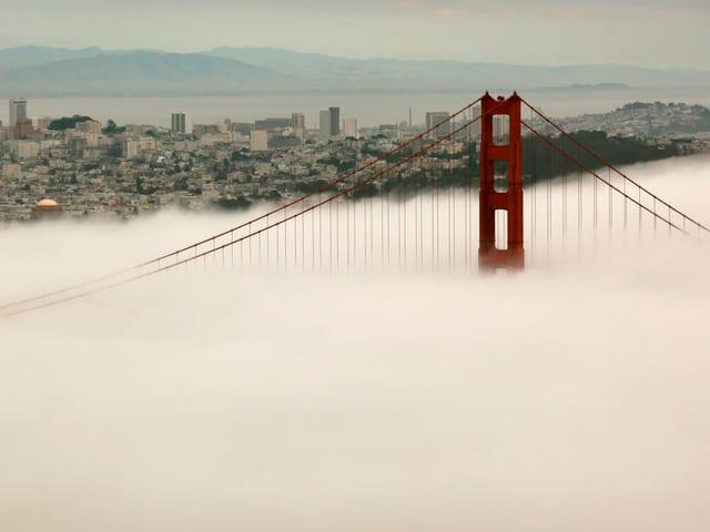 Im Vordergrund dichter Nebel, daraus ragt die rote Golden Gate Bridge hervor. Im Hintergrund die Häuser von San Francisco.
