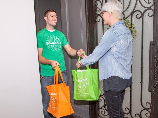 Ein Personal-Shopper bringt Einkaufstaschen an die Tür, wo ein Mann wartet.