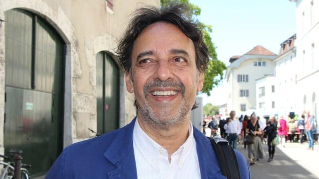 Ein Mann mit dunklen Haaren, Dreitagebart, weissem Hemd und blauem Jackett strahlt in der Altstadt von Solothurn.
