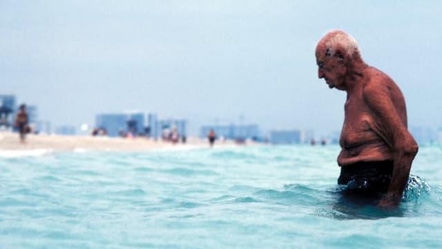 Ein alter Mann im Meer watet gebückt durch das Wasser in Richtung Strand
