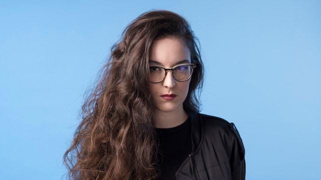 Eine junge Frau vor blauem Hintergrund.