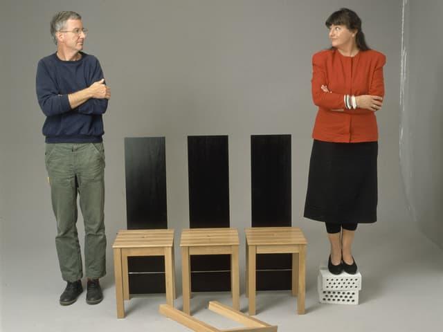 Ein Mann und eine Frau blicken sich an, zwischen ihnen stehen drei Tabourets mit schwarzen Rückenlehnen.