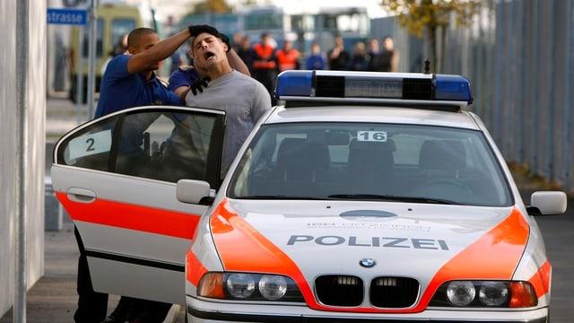 Ein Polizist stösst einen Zivilisten in ein Polizeiauto