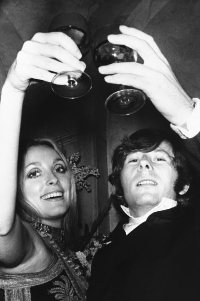 Sharon Tate und Roman Polanski stossen mit zwei Gläsern an (Bild in schwarz-weiss).