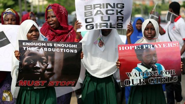 Frauen halten Transparente und fordern damit die Entführer auf, die Kinder zurückzubringen