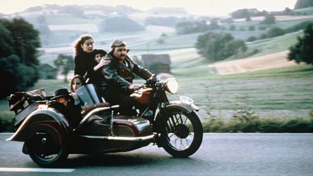 Eine Familie fährt auf einem Motorad mit Seitenwagen.