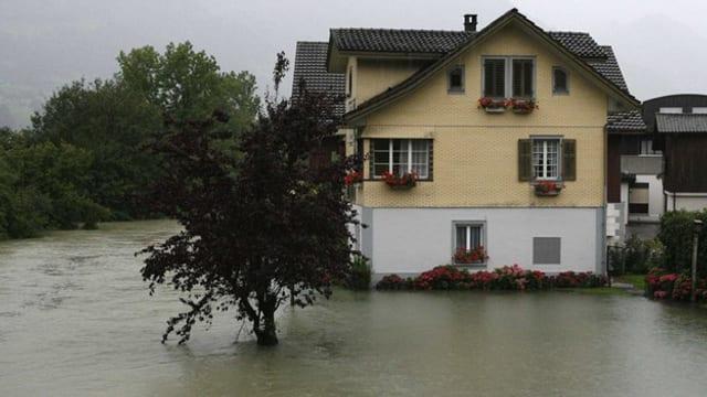Ein Haus und rundherum Wasser eines Flusses, der über die Ufer getreten ist.