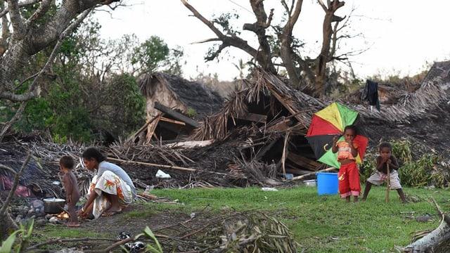 Eine Familie inzwischen zerstörter Häuser und umgefallenen Bäumen.