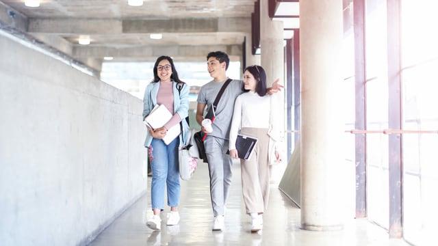 Drei junge Menschen laufen durch den Gang eines grossen Gebäudes.