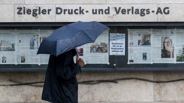 Ein Mann unter Regenschirm steht vor dem Gebäude der Druckerei in Winterthur.