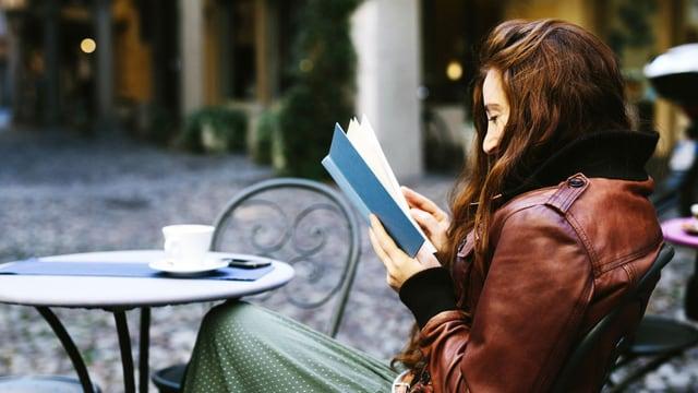 Eine junge Frau in einem Strassencafé, in einem Buch lesend.