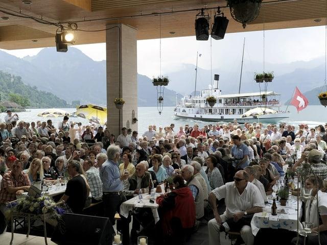 Foto aus dem Pavillon in Weggis aufgenommen mit Blick über das Publikum hinweg auf den See, wo ein Schiff mit Schweizerfahnezu sehen ist.