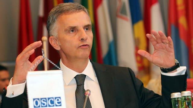 Burkhalter spricht bei seiner Antrittsrede bei der OSZE in Wien Mitte Januar in ein Mikrofon, hinter ihm sind diverse Landesflaggen erkennbar.