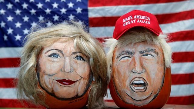 Karikaturen von Clinton und Trump vor einer US-Flagge.