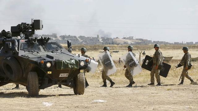 Türkische Soldaten mit Plexiglas-Schutzschilden gehen auf ein gepanzertes Militärfahrzeug zu.