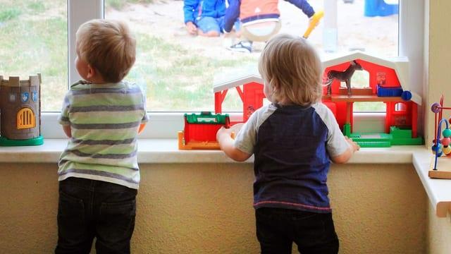 Zwei Kinder schauen aus dem Fenster