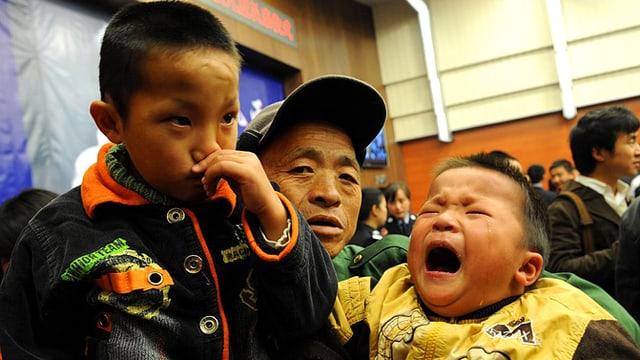 Zwei gerettetet Jungs in den Armen ihres Vaters. Der jüngere Bub weint. Foto von 2009.
