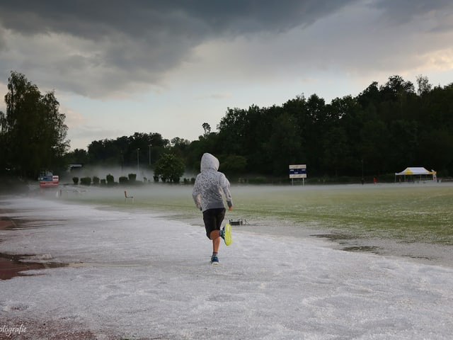 Ein Jogger läuft bei  Hageauf einer Sportanlage, seine helle Regenjacke schützt ihn nur wenig.
