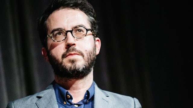 Ein junger Mann mit Brille und krausem Haar blickt nachdenklich.