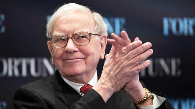 Warren Buffett lächelt und klatscht in die Hände