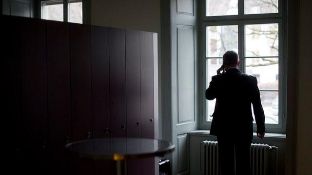 Bernhard Koch steht in einem dunklen Raum und telefoniert, während er zum Fenster hinaus schaut.