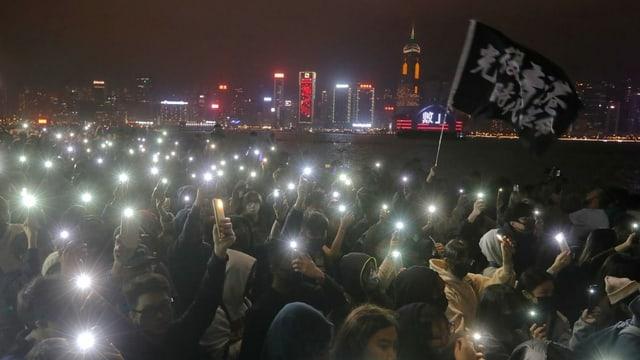 Eine Menschenmenge zündet kleine Lichter an am Flussufer in Hongkong.