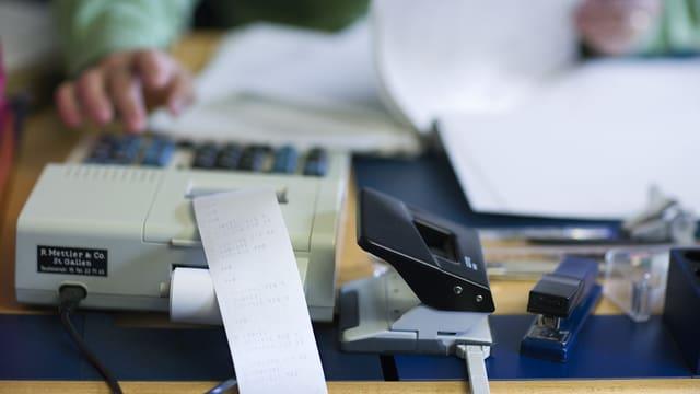 Ein Pult mit einem Papierberg und einer Rechenmaschine, auf der eine Hand etwas eintippt.