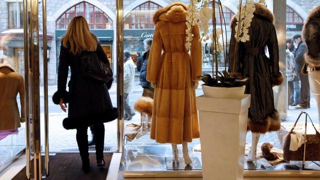 Eine Frau verlässt ein Kleidergeschäft in St. Moritz.