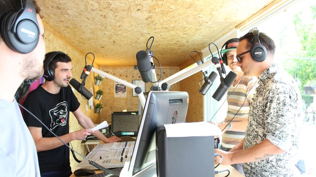 Zwei junge Männer interviewen zwei Personen in einem improvisierten Radiostudio