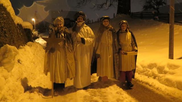 vier Sternsingerinnen stehen auf der verschneiten strasse