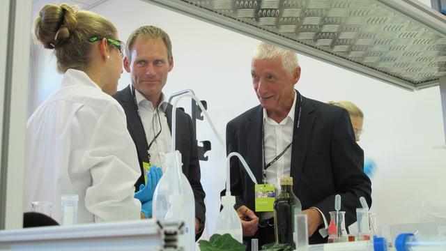 Eine Schülerin in Labormantel und mit Laborbrille erklärt zwei Besuchern des Jubiläum-Anlasses was sie macht.