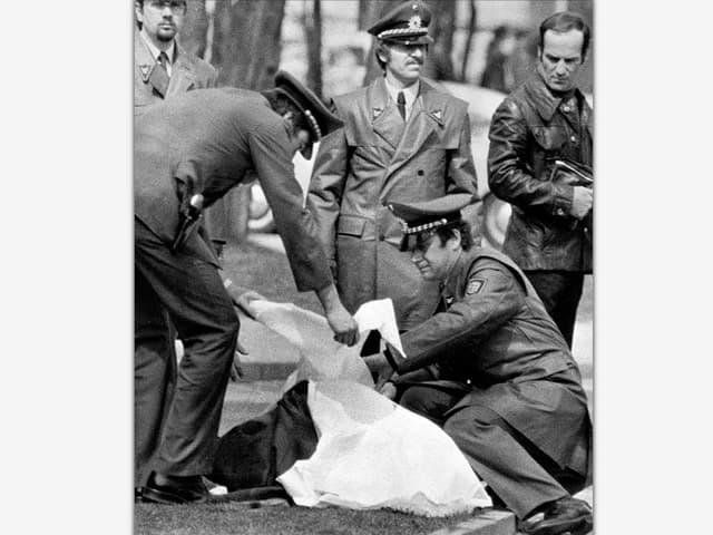 Polizisten decken am 7. April 1977 die Leiche von Generalbundesanwalt Siegfried Buback nach dessen Ermordung durch RAF-Terroristen ab.