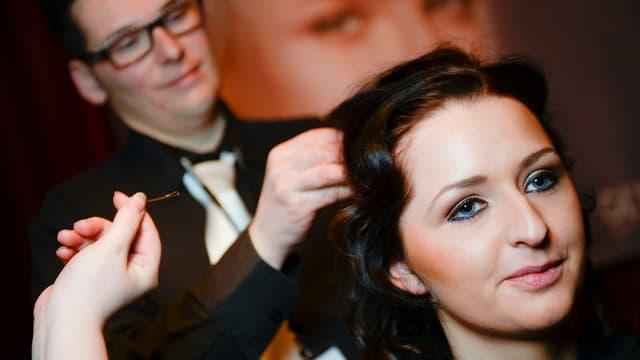 Symbolbild: Junge Frau wird vom Coiffeur coiffiert.