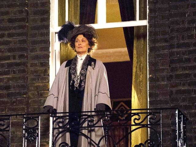 Eine Frau mit langem Gewand und Hut steht auf einem Balkon.