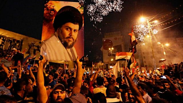 Anhänger von Muktada al-Sadr jubeln auf einer nächtlichen Strasse und halten ein Porträt von ihm in die Höhe.