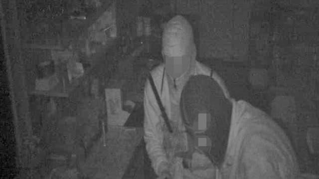 Ein verpixeltes Bild mit zwei maskierten Männern - schwarz-weiss.