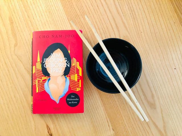 «Kim Jiyoung geboren 1982» von Cho Nam-Joo liegt auf einem Tisch mit Schüssel und Essstäbchen daneben