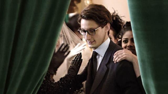Durch eine Öffnung eines grünen Vorhangs sieht man einen jungen Mann, der von Frauen beklatscht wird.