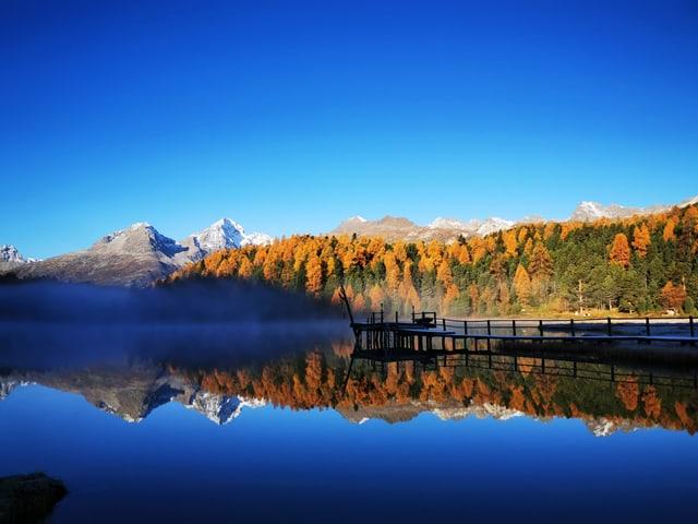 Stahlblauer Himmel ohne Wolken und Berglandschaft, die sich im See spiegelt